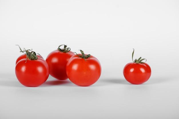 Losowo wybrane pomidory na białym tle z cieniami.