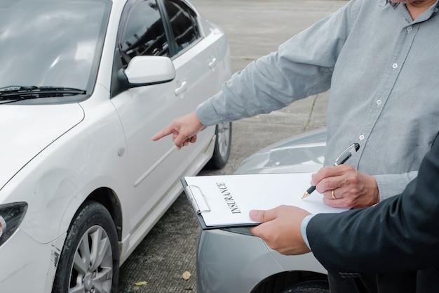 Loss adjuster insurance agent kontrolujący uszkodzony kierownik sprzedaży samochodu udzielający porad