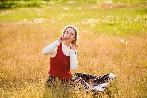 Łotewska kobieta w tradycyjnej odzieży pozowanie w polu na tle przyrody w miejscowości. festiwal ligo. ryga. łotwa