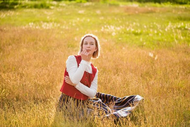 Łotewska kobieta w tradycyjnej odzieży w polu