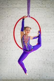 Lotnicze gimnastyka na kole, mała dziewczynka robi ćwiczenia