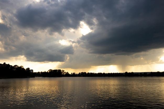Lotnicze niebo o zachodzie lub wschodzie słońca nad jeziorem otoczone rozproszonymi chmurami o różnych kolorach.