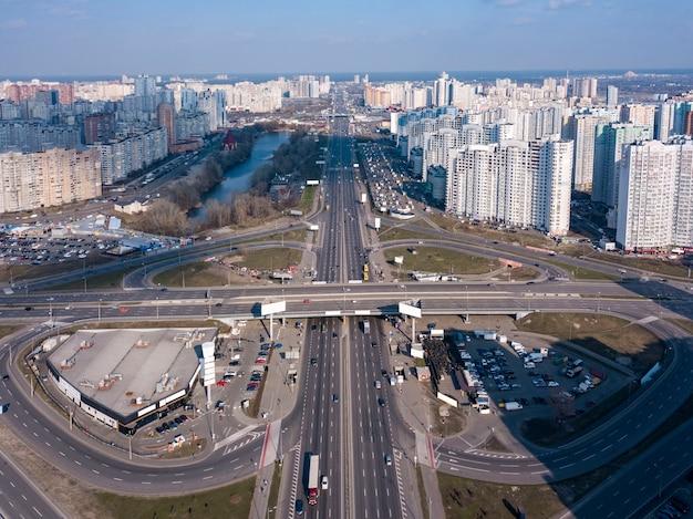 Lotnicze zdjęcie panoramiczne z drona, widok z lotu ptaka na dzielnicę pozniaky, al. mykoly bazhana z ruchem ulicznym i nowoczesnym budynkiem miasta kijów ukraina o zachodzie słońca.