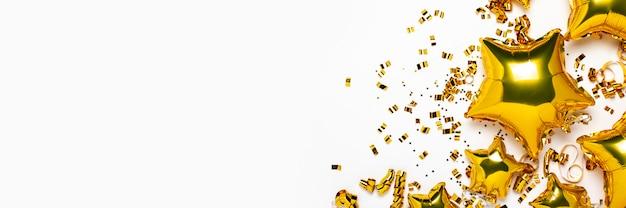 Lotnicze złote balony gwiazdowe i confetti kształtują na białym tle.