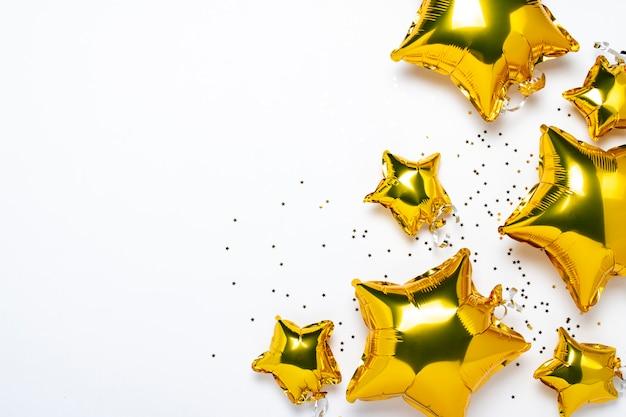 Lotnicze złote balony gwiazdują kształt i cukierek na białym tle.