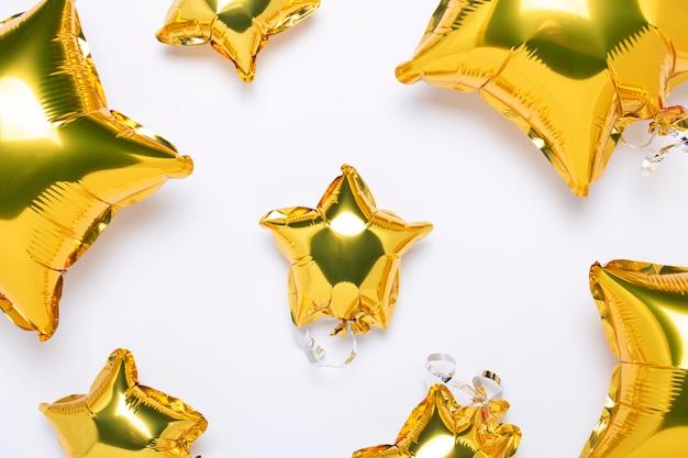 Lotnicze złote balony kształtują gwiazdę i cukierek na bielu