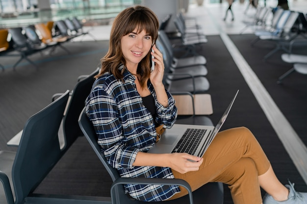 Lotnisko młoda kobieta pasażer z inteligentny telefon i laptop siedzi w hali terminali, czekając na jej lot