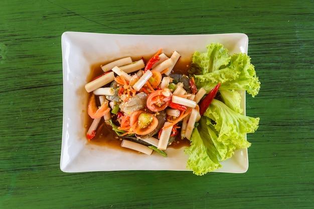Lotos łodyga tajska pikantna sałatka na zielonym stole, tajskie jedzenie lokalne.