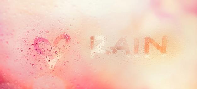 """""""love rain"""", widok przez przednią szybę silnego, deszczowego dnia. abstrakt rozmytego tła świateł bokeh."""