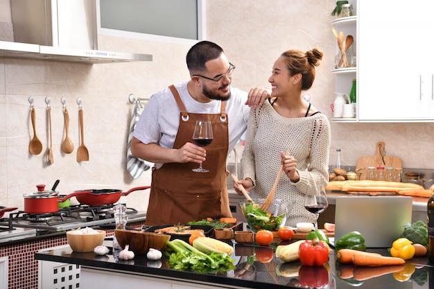 Loving młoda para azjatyckich gotowania w kuchni razem podejmowania zdrowej żywności i picia wina