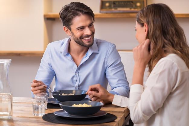 Loving para patrząc na siebie podczas lunchu. bliska strzał młodego mężczyzny i kobiety obiad w domu. szczęśliwa młoda para jedzenie.