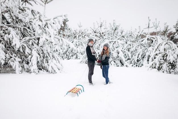 Loving para trzymając się za ręce w zimie w zaśnieżonym lesie