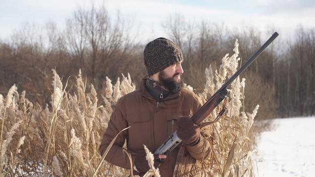Łowca z brodą zamierza polować na swoją zdobycz, zwierzynę, zbliżenie myśliwego