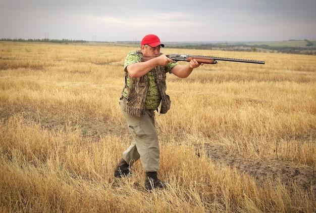 Łowca z pistoletem na polu celujący w zdobycz