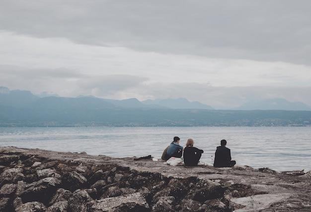 Lozanna, szwajcaria - 2 lipca 2017: ludzie relaksują się na nabrzeżu jeziora genewskiego w lozannie szwajcaria, europa. dramatyczne błękitne niebo i letni krajobraz