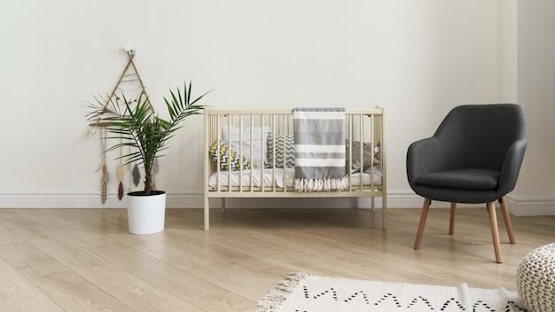 Łóżeczko dziecięce i nowoczesny szary fotel oraz roślina pokojowa w dziecięcej sypialni