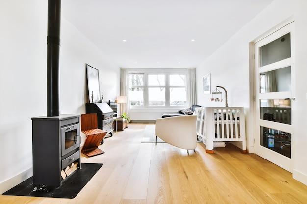 Łóżeczko dziecięce w białym salonie z kominkiem i sofą przy oknie w świetle dziennym