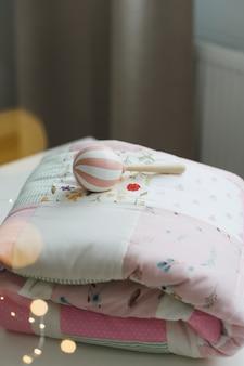 Łóżeczko dziecięce z różowym patchworkowym kocykiem i tekstyliami dla dzieci