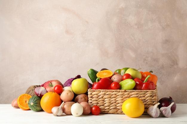 Łozinowy kosz, warzywa i owoc na białej drewnianej przestrzeni dla teksta