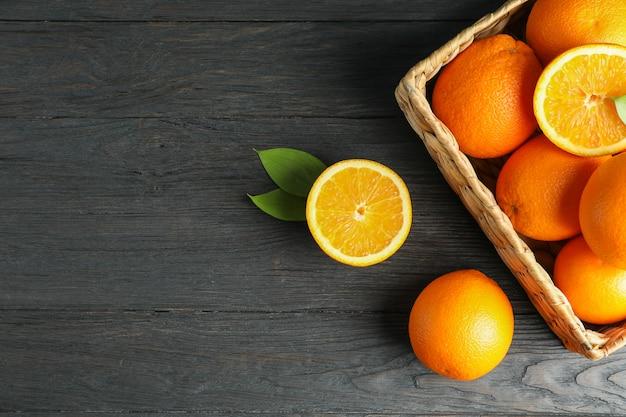 Łozinowy kosz z dojrzałymi pomarańczami na drewnianym stole.