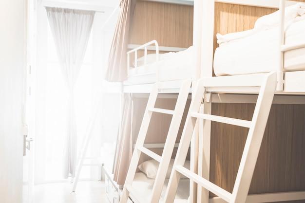 Łóżka w pokoju hostelowym dla turystów lub studentów rozmyte na tle baneru