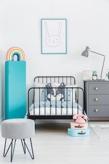 Łóżko dziecięce z czarną metalową ramą pośrodku pastelowego wnętrza sypialni scandi prawdziwe zdjęcie