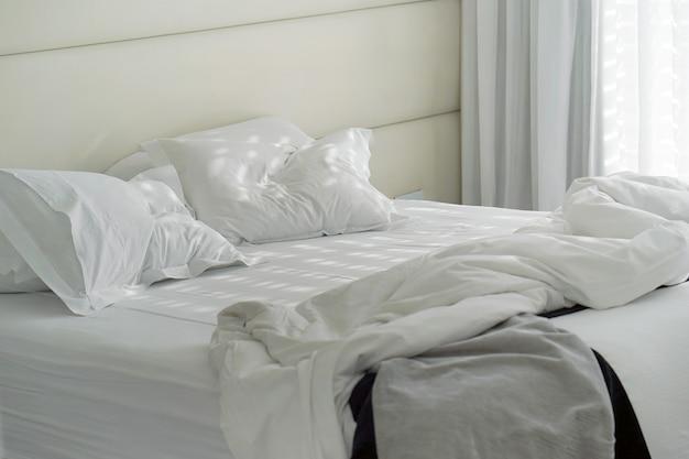 Łóżko hotelowe po użyciu. pokój koc poduszki brudne łóżko.