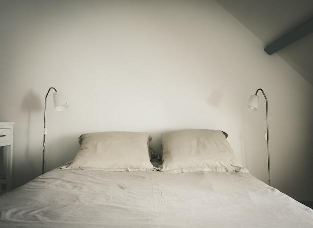 Łóżko i lampa w białej sypialni. tło białe ściany