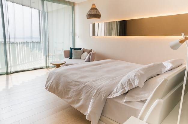 Łóżko king size z białą pościelą i poduszką na łóżku w pokoju hotelowym.