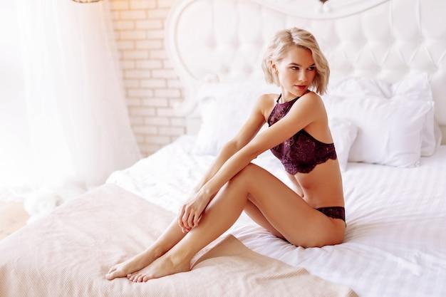 Łóżko królewskich rozmiarów. szczupła, atrakcyjna dziewczyna siedzi na białym łóżku typu queen-size w mieszkaniu