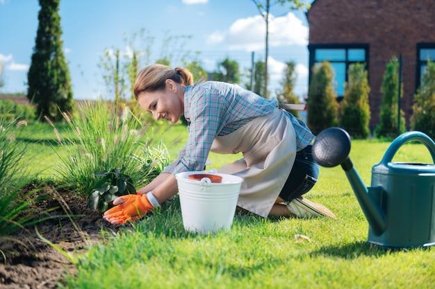 Łóżko ogrodowe. ładna kobieta czuje się radosna i szczęśliwa, opierając się na swoim ogrodowym łóżku, sadząc nowe małe kwiatki