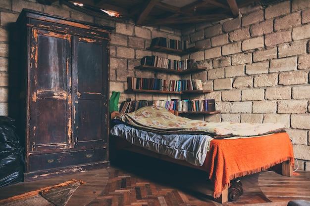 Łóżko pojedyncze sfatygowane półki szafy z książkami w rogu na tle ściany
