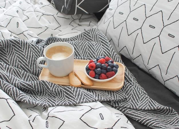 Łóżko śniadaniowe drewniana taca wnętrze wcześnie rano miejsce kopiowania geometryczny prześcieradło i poszewka na poduszkę jagody ciasteczka cappuccino