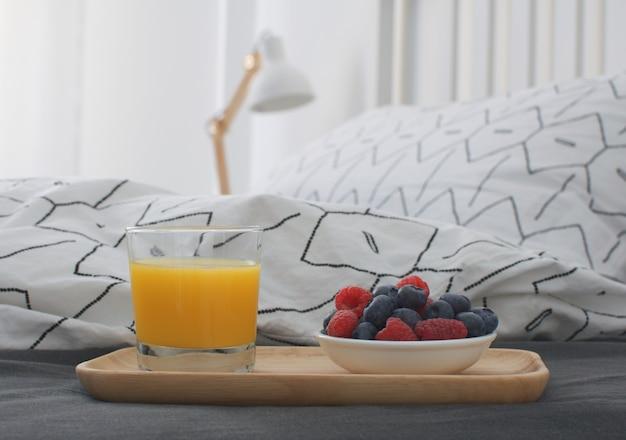 Łóżko śniadaniowe drewniana taca wnętrze wcześnie rano miejsce kopiowania geometryczny prześcieradło i poszewka na poduszkę jagody sok pomarańczowy ciastka