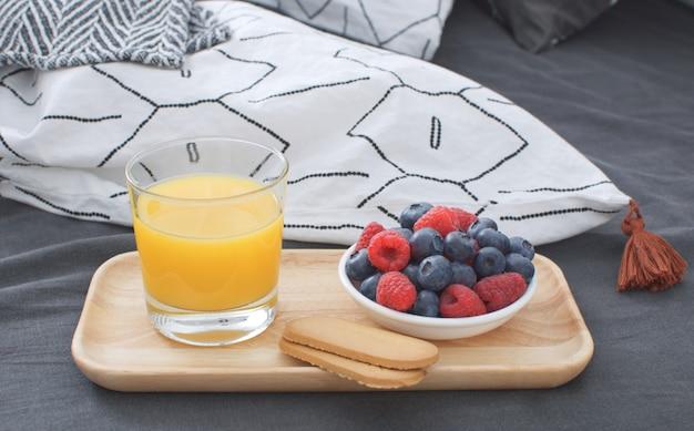 Łóżko śniadaniowe drewniana taca wnętrze wcześnie rano prześcieradło geometryczne i poszewka na poduszkę jagody sok pomarańczowy ciastka