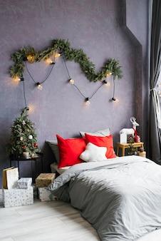 Łóżko we wnętrzu pokoju w stylu skandynawskim z choinką