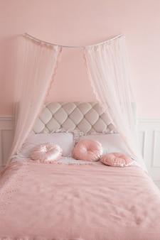 Łóżko z baldachimem i różowymi poduszkami.