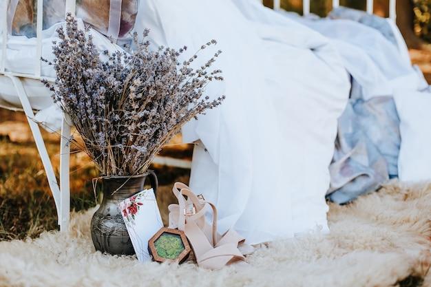 Łóżko z baldachimem ze strefą fotograficzną z butami, kwiatami, zaproszeniem do natury. tkanina powiewa na wietrze. miejsce na zdjęcie panny młodej. sesja fotograficzna