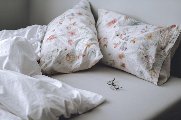 Łóżko z białym kocem i poduszkami rano. komfort w domu