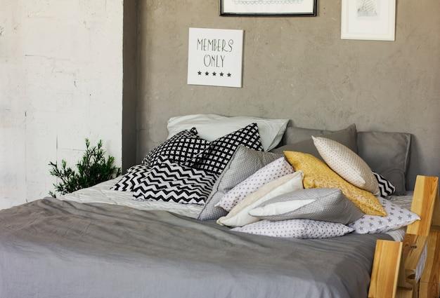 Łóżko z poduszkami w pokoju na poddaszu. betonowe ściany, plakaty. skandynawskie wnętrze