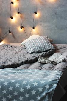 Łóżko z poduszkami w pokoju na poddaszu, betonowe ściany z girlandą żarówek. skandynawskie wnętrze