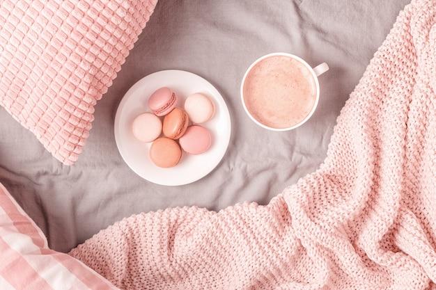 Łóżko z różową dzianinową kratą, kawą i makaronikami