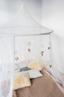 Łóżko z wzorzystą pościelą i białymi zasłonami