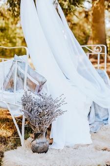 Łóżko ze strefą foto z baldachimem z kwiatami lawendy do natury. tkanina powiewa na wietrze. miejsce na zdjęcie panny młodej. sesja fotograficzna