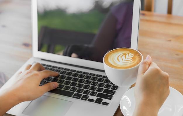 Lperson pracuje na laptopie z filiżanką kawy obok