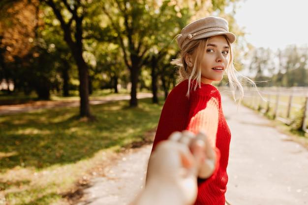 Lśniąca blondynka patrząc czarująco za osobą na ścieżce w parku.