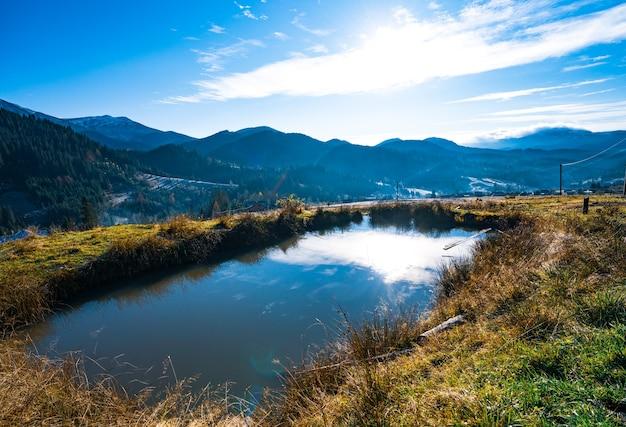 Lśniąca kałuża na wiosennym zielonym polu na niezwykłych wzgórzach