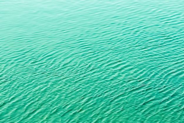 Lśniące zielone faliste wody powierzchni marszczyć tło