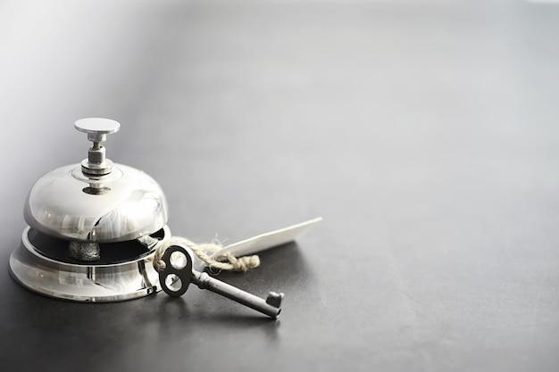 Lśniący srebrny metalowy dzwonek w recepcji hotelu. stół w hotelu przy portierni z dzwonkiem i kluczem do drzwi. klucz i dzwonek w hotelu.