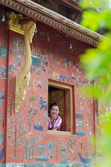 Luangprabang, laos: 22 kwietnia 2017 - kobieta w buddyjskim kościele uśmiechając się do wat xieng thong świątyni światowego dziedzictwa przy aril 22,2017, luang pra bang, laos